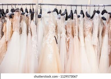 Many luxury wedding dresses in bridal salon.