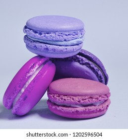 Many macaroons on violet neon background. Minimalism