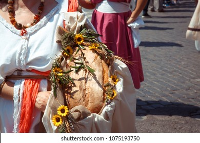 Many of the maidens within Rome's birthday parade carried traditional foods, masks, flowers, and wild animals.  Shown here, the parade is marching near the Colisem.