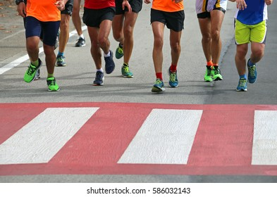 many marathon athletes run very fast over the pedestrian crossing in the city during the sports challenge