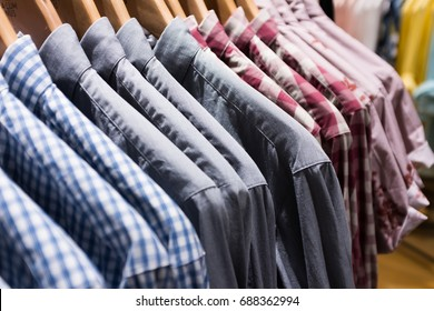 Many men shirts hanging on a rack in the shopping mall