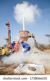 Many men wearing very colourful personal protective equipment (PPE) are sieving and drilling and working with white dust at a gold mine in Namibia