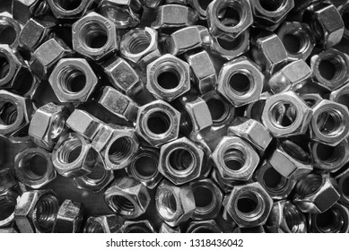 Many metal nuts in black and white. Natural photo.