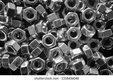 Many metal nuts on black and white color. Abstract industry background. Natural photo.
