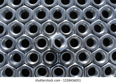 Many metal nuts on black background. Abstract industry background. Natural photo.