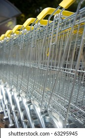 Many metal shopping carts with yellow handles outdoor