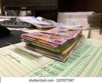 Many mexican pesos bills over a desk inside a small business office