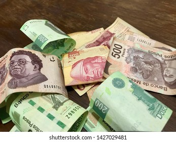 Many mexican pesos bills spread over a wooden desk inside a small business office