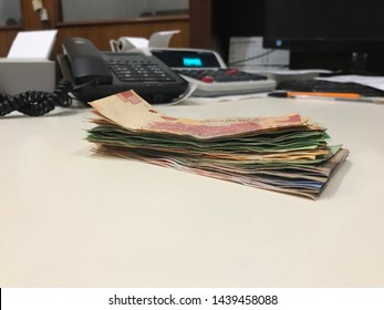 Many mexican pesos bills spread over a beige colored desk inside a small business office