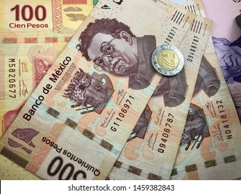 Many mexican pesos bills spread over a wooden desk