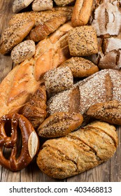Many mixed breads, rolls and pretzels on an rustic wooden table.