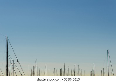 many modern ship masts rising into a beautiful and colorful clear sky