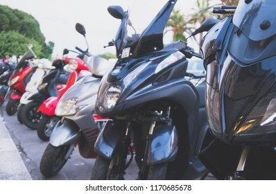 Many mopeds and scooter motorcycles parked on the street.