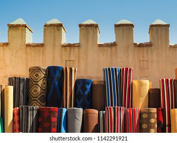 many moroccan carpet outside at a bazar in a arabic city with blue sky in the back
