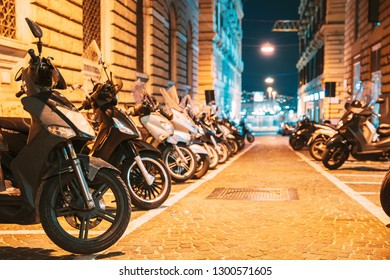 Many Motorbikes, Motorcycles Parked In European City. Scooters Parked On Night Street In European City