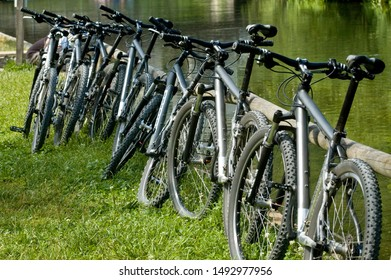 Many mountain bikes parked at a rail near a small river
