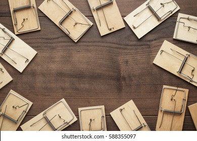 many mousetraps on the brown wooden background