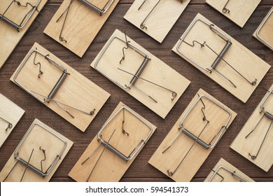 many mousetraps in order on the brown wooden background