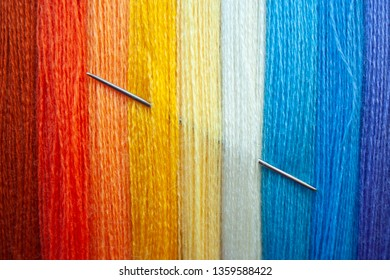 Many multi colored yarn strings for design background. Texture of colored thread with needle in it. Concept of sewing, hobby image.