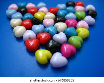 Many multi-colored beads in the shape of heart closeup