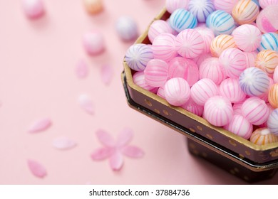 Many multicolored candy and petal are placed on the table.