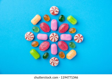 Many multicolored delicious caramel candies on a blue background