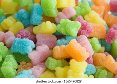 Many multicolored jelly gummy bears.Yellow, orange, red, pink, blue and green jelly bears on a pile. Sweet background in sugar.