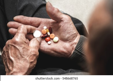 Many multi-colored pills in a Senior's hands. Painful old age. Caring for the health of the elderly