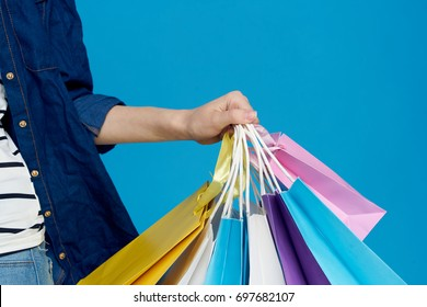 Many multi-colored shopping bags on a blue background close-up
