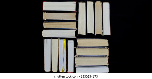Many multicolored thick open books stand on a dark background. On the books are old round glasses and an open notebook with a pencil.