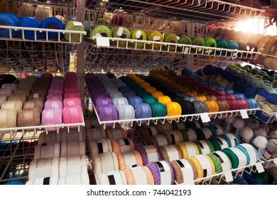 Many multi-colored threads on the shelf of the store.