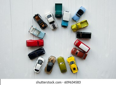 Many multi-colored toy cars on white background. The group of car toy in a circle. Small cars on white table, top view with copy space. Traffic jam concept with multiple toy cars on a blackboard.