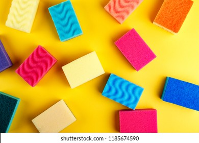 many multi-colored washcloths are scattered on a bright yellow background
