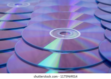 Many musical clean compact discs with a rainbow spectrum of colors as a bright background