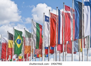 Many national flags against a beautiful cloudy sky.