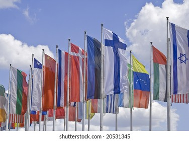 Many national flags against a beuatiful cloudy sky.