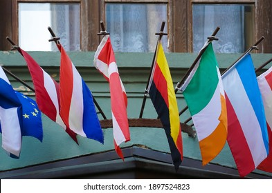 many national flags of different states  on historical building in Europe. Worldwide, international Flags. green building with big window frame.