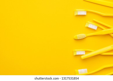 many new plastic toothbrushes on the yellow background with copy space