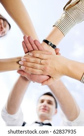 Many office workers holding hands all together across the blue sky demonstrating unity and team work outdoors.
