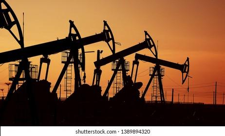 De nombreuses pompes à huile au coucher du soleil sous le ciel rouge