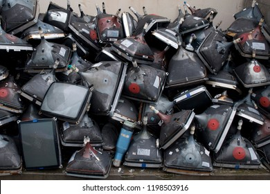 Many old cathode ray tube televisions stacked in a pile