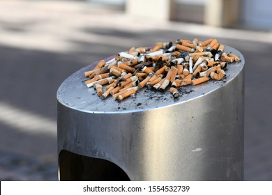 Many old cigarette stubs spilling over from ashtray of overflowing public trash bin