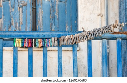 Many old clothespins are strung together on a line outside on a blue wooden balcony parapet in a Greek village
