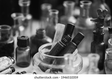 Many Old Deutsch Vintage Medical Glass Capacity. Detail Of Retro Chemical Pharmaceutical Science Researches. Small Bottles Different Sizes From Times Of World War II. WW2 WWII. Black And White
