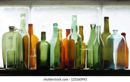 Many old glass bottles on windowsill. Closeup, daylight.