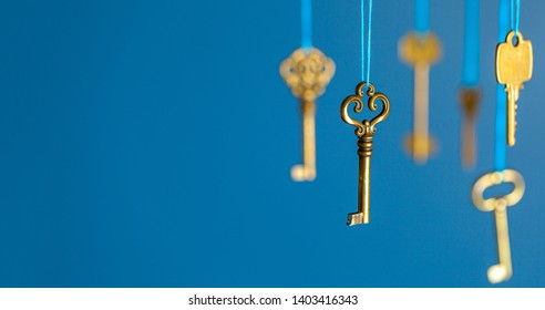 Many old keys of yellow gold color are hanging on thread on a blue background. The concept of the selection of access or password to the secret data. Copy space for text