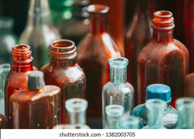 Many Old Medical  Glass Capacity. Detail Of Retro Chemical Pharmaceutical Science Researches. Many Small Vintage Bottles And Glassware Different Sizes And Colors.