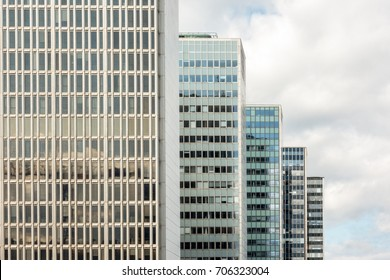 Many old tall office buildings in a row with cloudy sky. Horizontal view.