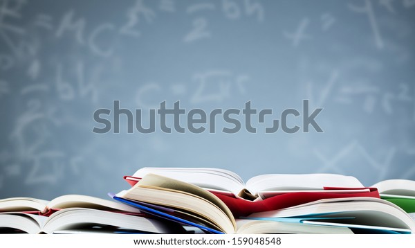 Many open books lying flat before a blue background with various formulas and letters.