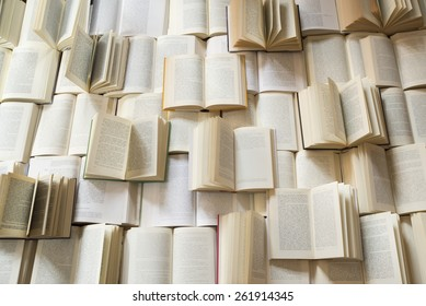Many open books piled up. unreadable text